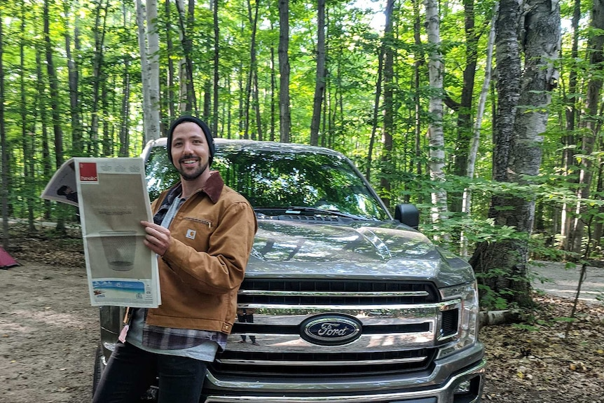 Alex McClintock smiles and stands beside a four-wheel drive, while holding a newspaper.