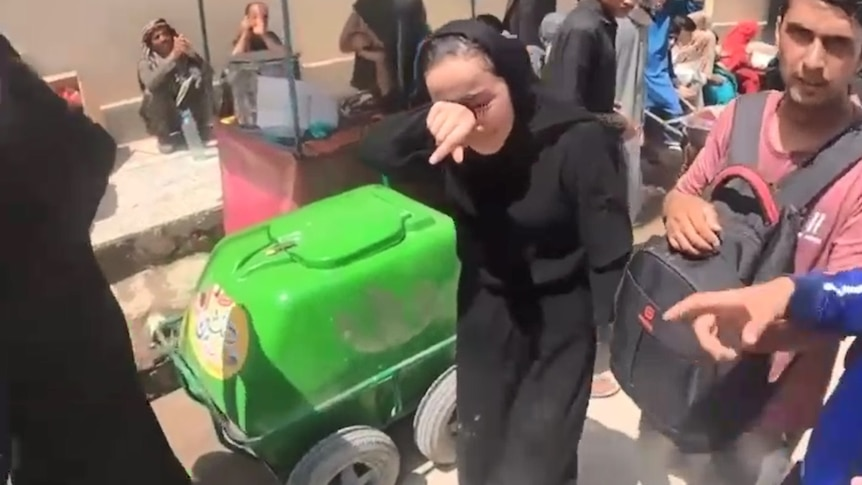 Zakia Khudadadi cries and wipes her face wearing black with people around her