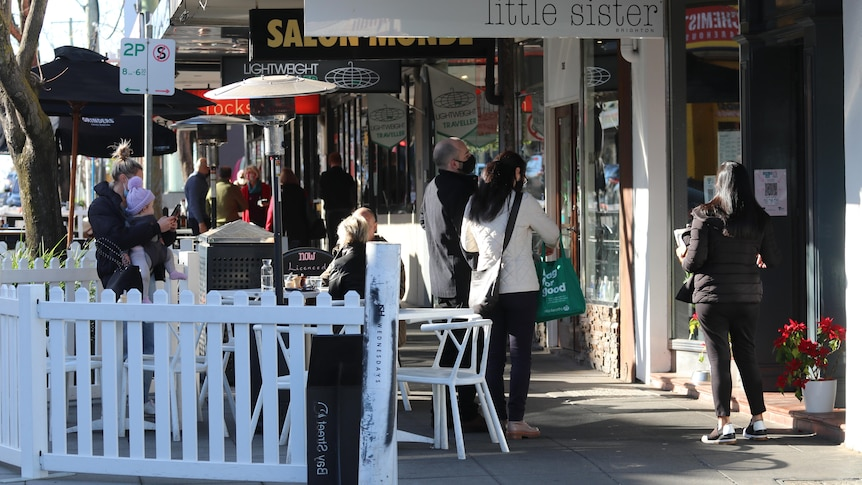 A handful of masked people check in on QR codes and stand outside a suburban cafe in Brighton.