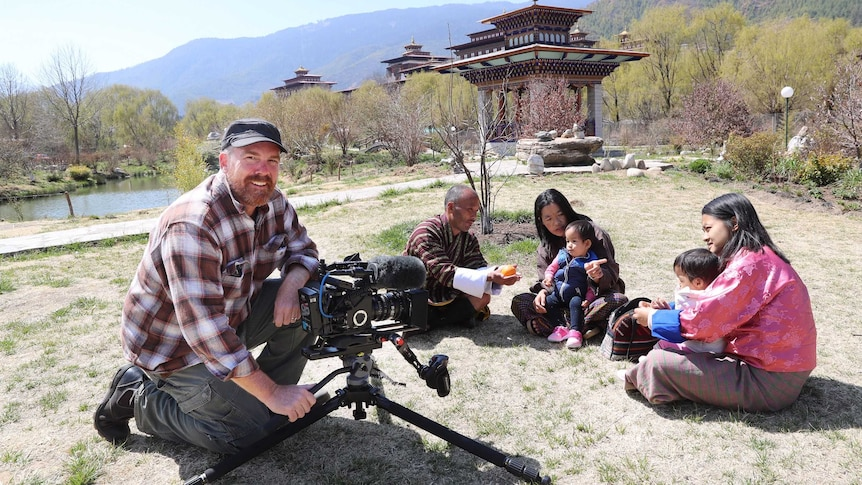 Smith with camera filming twins and their family sitting on grass outside with temples in background.