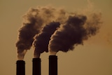 A file image of smoke stacks against a yellowish sky.