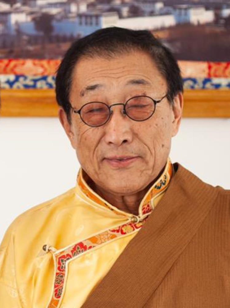 A profile photograph of an elderly Tibetan man in traditional dress.