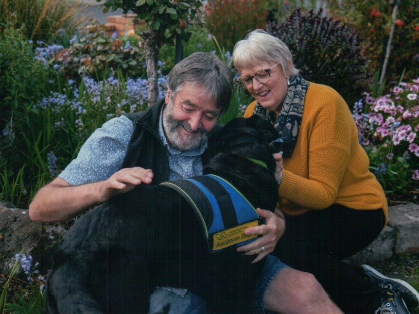 A man and a woman outside in a backyard garden hugging a black assistance dog