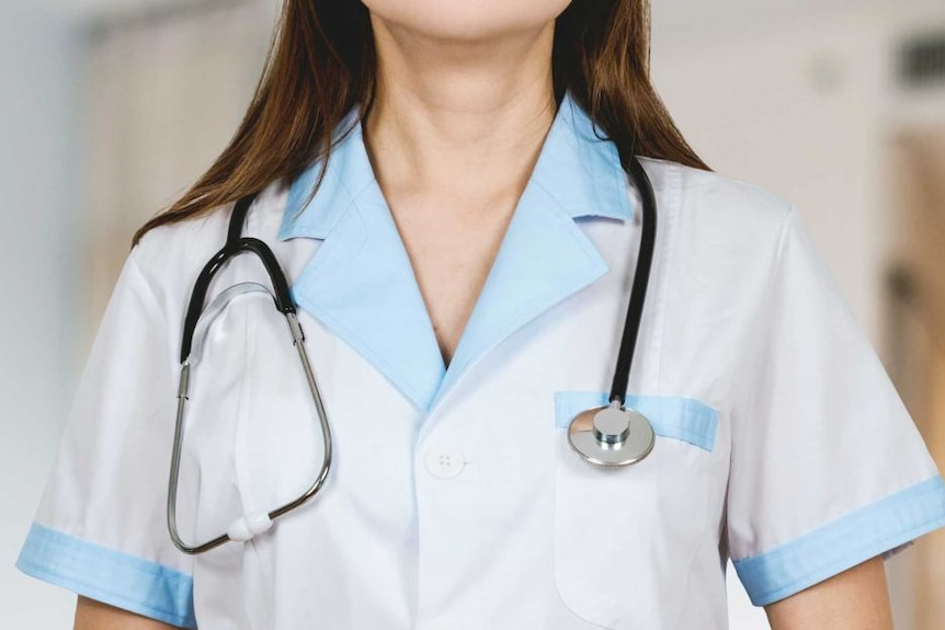 A female in a doctor's uniform stands with a stethoscope around her neck.