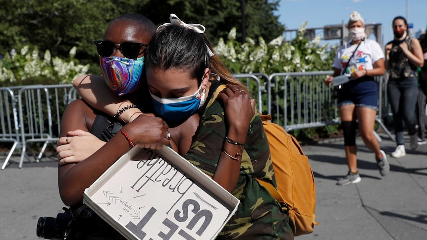 Two African American protesters hug holding a sign saying 'let us breathe'