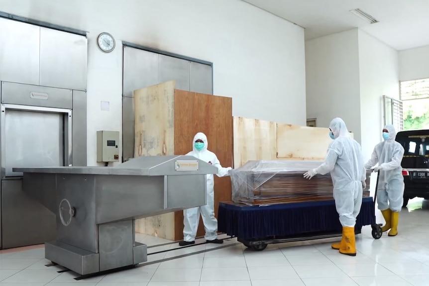 Di dalam krematorium di dalam kamar mayat berdiri dua pria dengan pakaian pelindung.