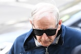 Marist Brother Gerard McNamara enters the Victorian County Court wearing dark sunglasses.