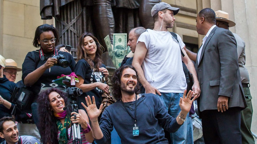 Actor Russell Brand kneels on concrete statute with smiling protestors behind him taking photos.