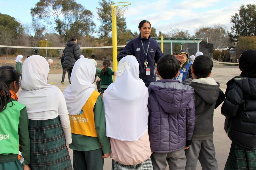 Primary school kids stand on a netball court listening to a netball player giving instructions.