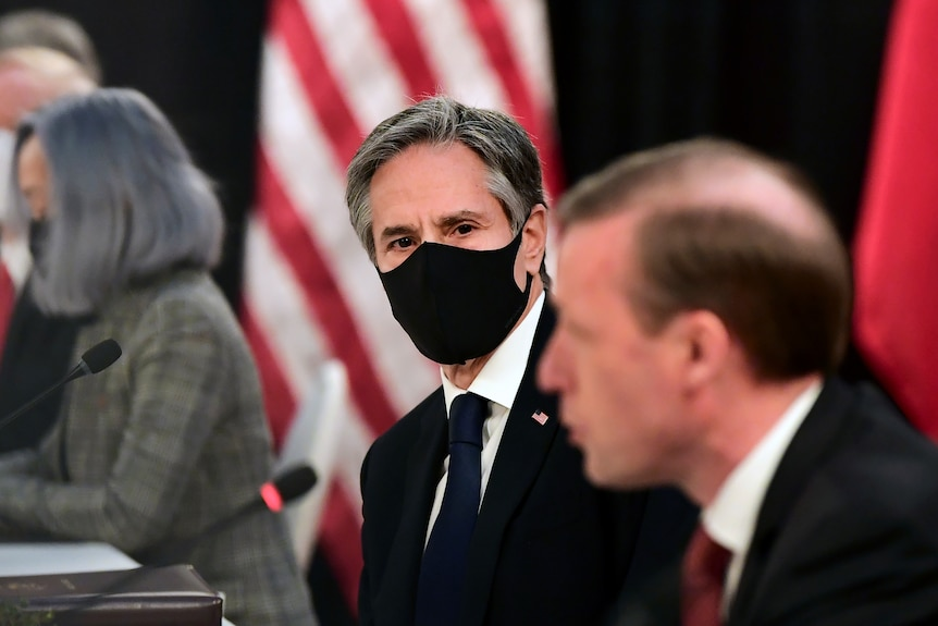 A man in a face masks looks at another man who isn't wearing a face mask as he talks into thin microphone.