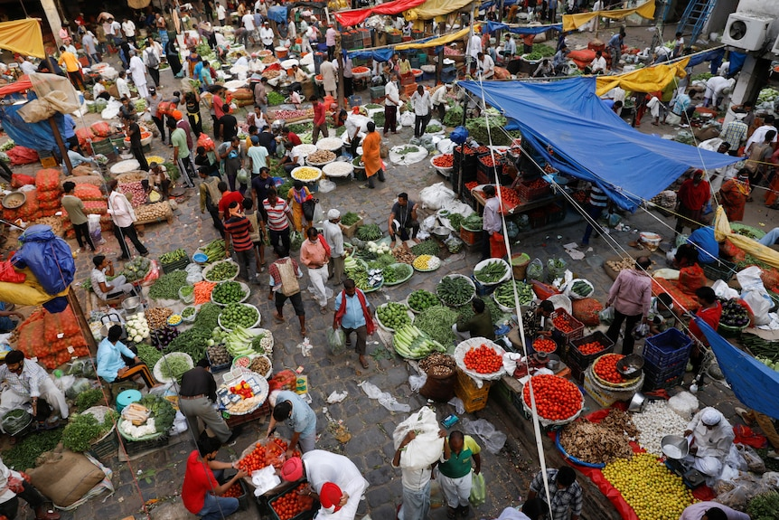 People shop at a crowded wholesale vegetable market in Delhi