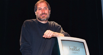 Steve Jobs leans on a new iMac computer with his elbow in 1998.