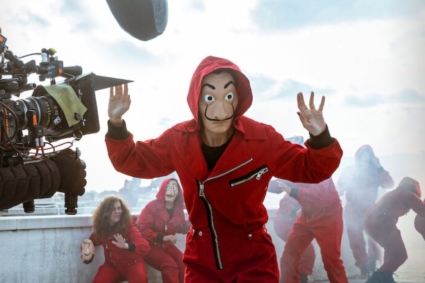 A person in a red jump suit and mask puts their hands up with a film camera in shot