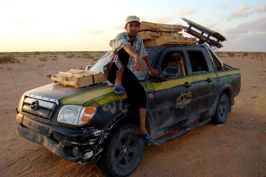 A man sits on the bonnet of a truck loaded with weapons.