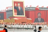 Performers travel past Tiananmen Square with a float showing a large portrait of Chinese President Xi Jinping