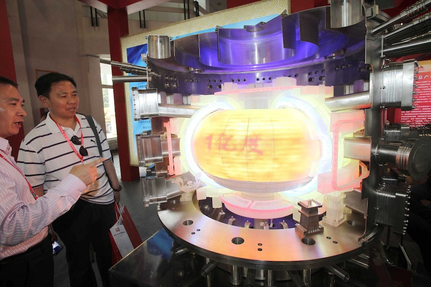 People look at a model of ITER