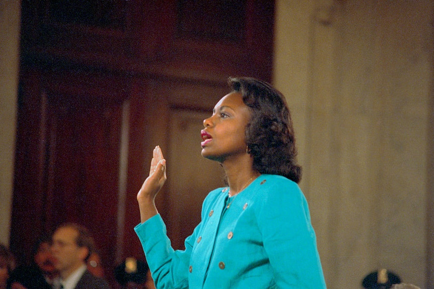 Anita Hill with one hand in the air