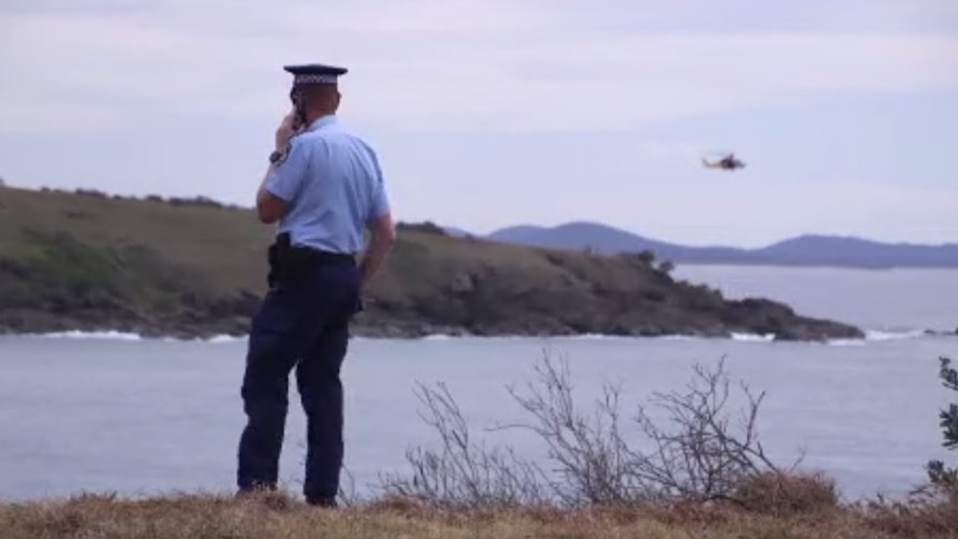 A policeman in short-sleeves stands on a hill overlooking the sea as a helicopter flies low over rocky coast in the distance