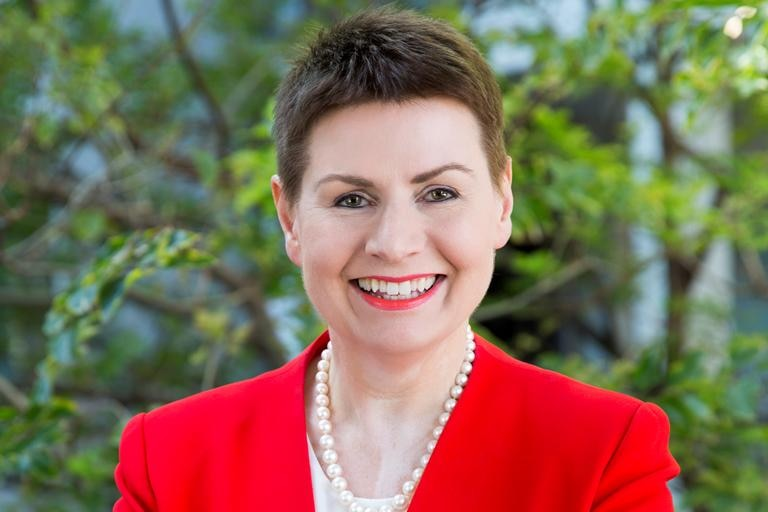 A woman with short brown hair, in a bright red formal jacket, with arms crossed, smiling.