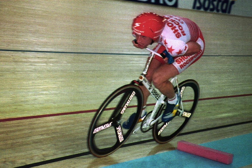 A cyclist rides a bike with his arms hunched next to him on a wooden track