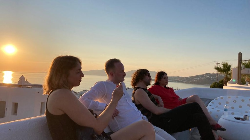 Jessica Wong and her friends sit on a rooftop in Mykonos with the sun setting over the Mediterranean.