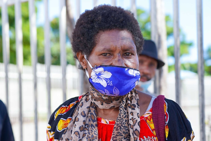 A Papua New Guinean woman in a bright dress and tropical print face mask