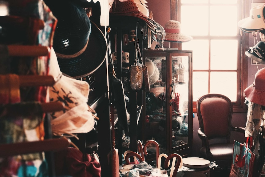 Cluttered room with hats, umbrellas, cabinets, bags, etc depicting the amount of clutter one person can accumulate in a life.