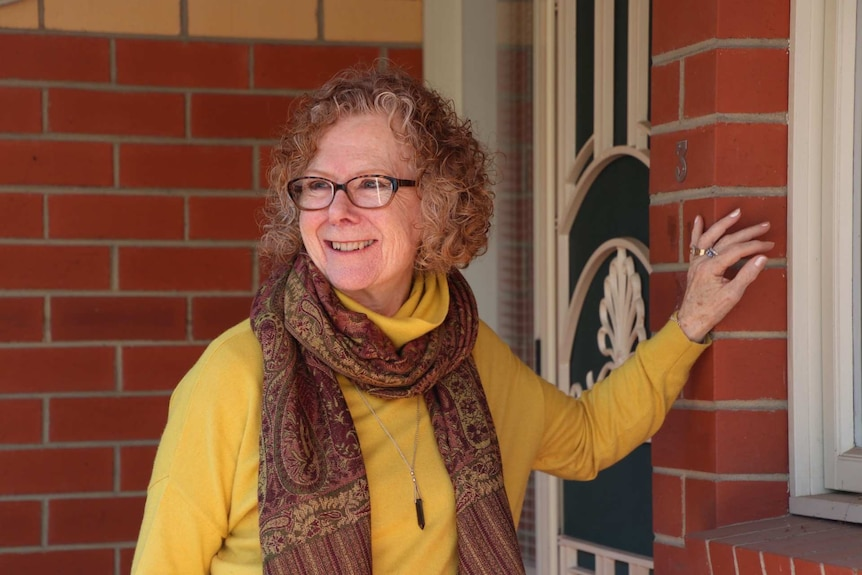 A woman wearing glasses and a patterned maroon scarf smiles while standing before the front door of a brick house.
