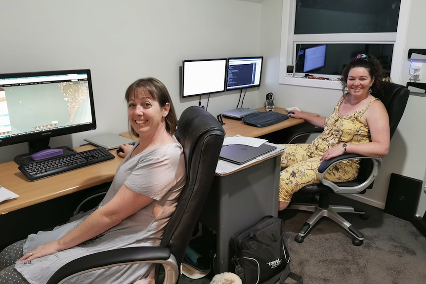 Two casually dressed, smiling middle-aged women sit at computer desks in a room at night.
