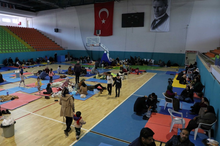 In a sports gymnasium, you view a group of people resting on its wooden basketball floor on brightly-coloured mats.