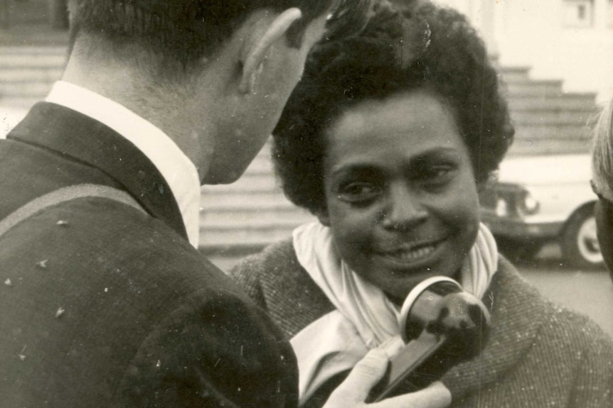A young woman speaks to a journalist in the street.
