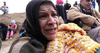 A woman holding a baby cries.