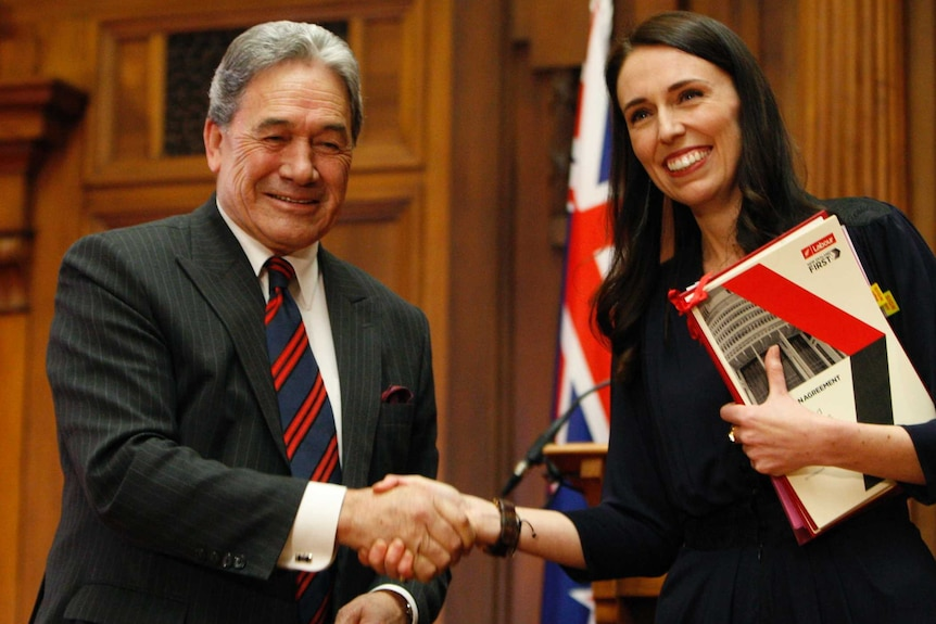 Winston Peters shakes hands with Jacinda Ardern after they sign a coalition agreement.