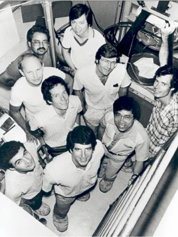 A black-and-white photo of mine smiling men in shirt sleeves