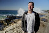 Man with black hair in white t-shirt and grey hoodie stands on beach with waves crashing on rocks behind him on a sunny day