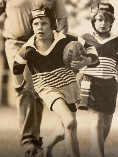 Old photo of little boy wearing head gear while playing rugby league