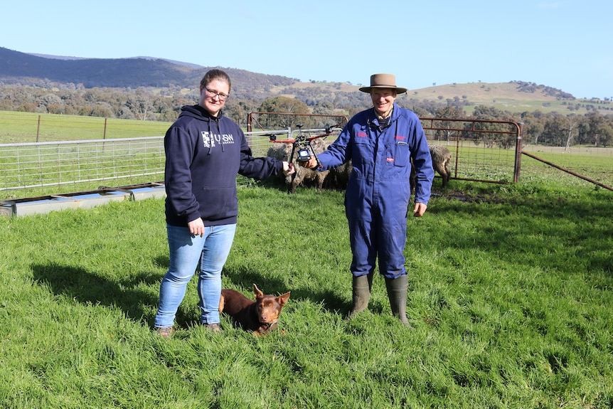 Woman and man in a paddock holding a drone between them, brown dog sitting on the ground between them.