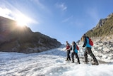 Three people walking along a glacier during the day.