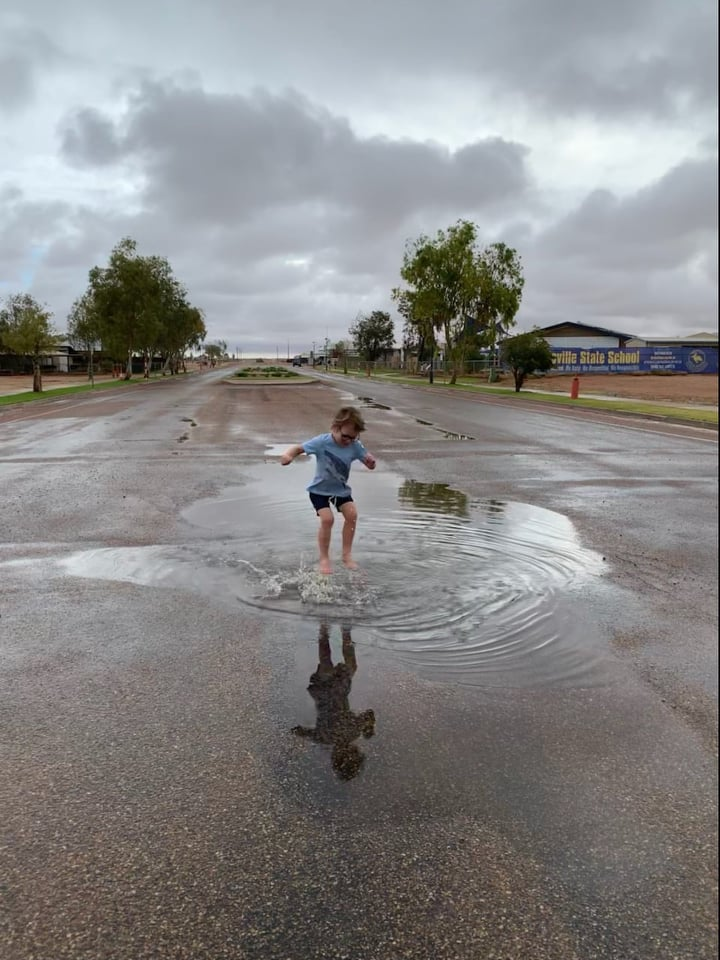 Little boy jumps in rain puddle in the middle of the street