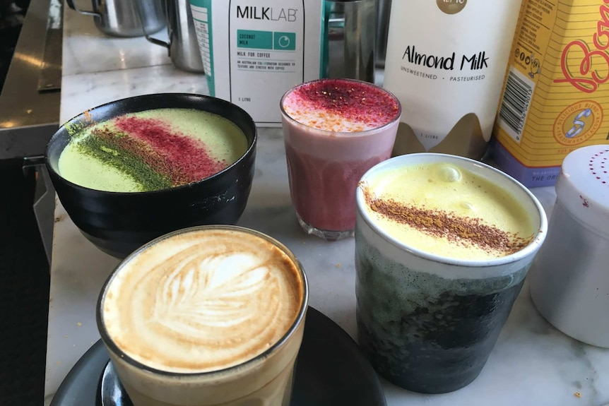 Four coffees rest on a bench; they are brown, green, yellow and pink.