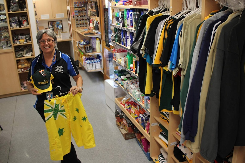 A woman holds a pair of green and gold Aussie shorts in front of her inside a small shop.