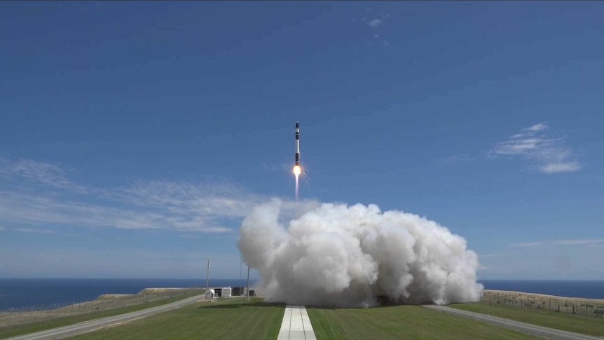 A rocket going up into the sky above a huge cloud