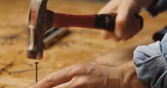 Unidentified man nailing with hammer