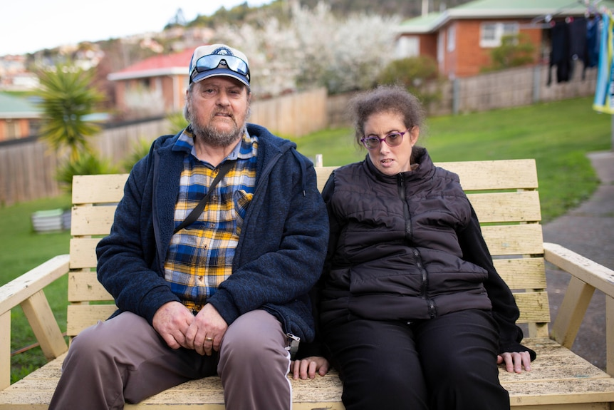 A woman and her father sit on a bench waiting for a bus.