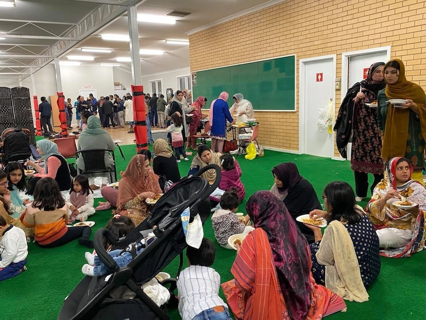 People sitting and standing in a hall eating food together.
