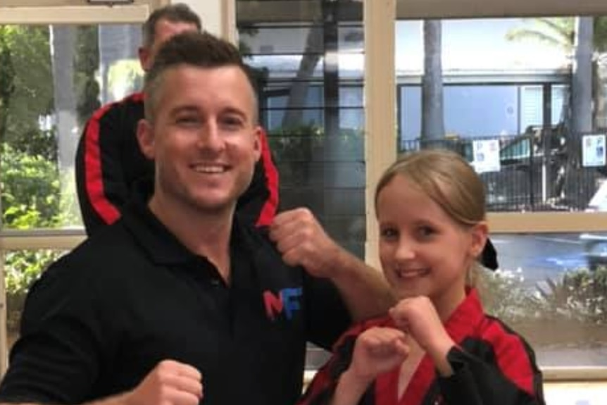 Man and a young girl pose with fists up