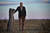 Ross Garnaut leans on a dead tree.