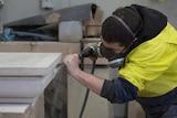 A stonemason carving a piece of stone