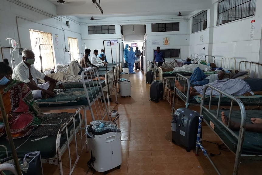 Oxygen machines on the floor in a ward filled with sick patients