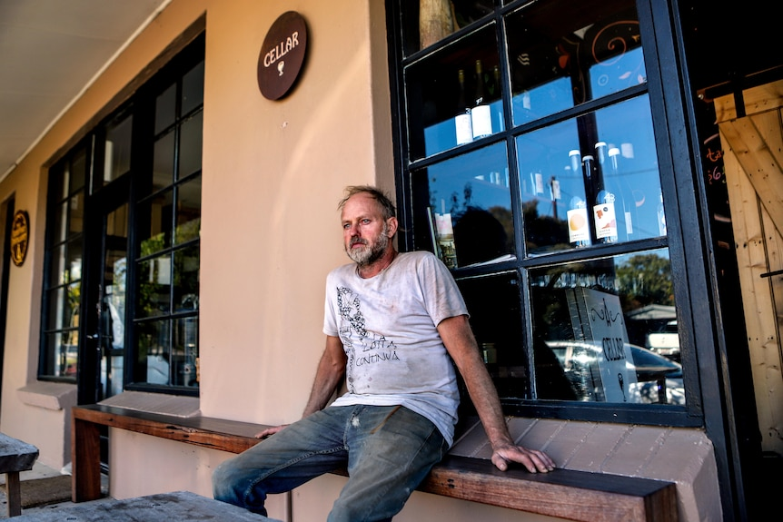Man with thinning grey hair and white t-shirt sits outside restaurant with wine bottles in window